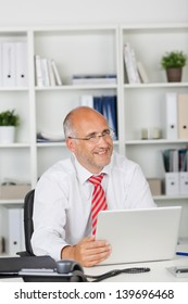happy businessman with laptop looking to side