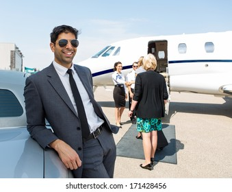 Happy businessman leaning on car with airhostess and pilot greeting business people against private jet