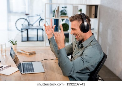 happy businessman listening music in headphones and looking at laptop while showing rock sign in office