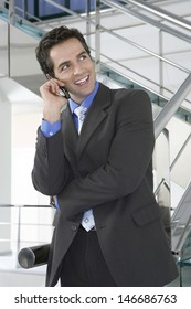 Happy businessman looking away while using mobile phone by railing in office