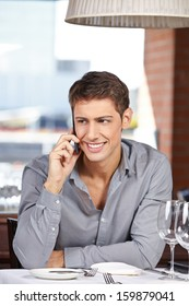 Happy businessman making call with his smartphone in a restaurant