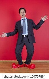Happy businessman next to a red wall with clown shoes