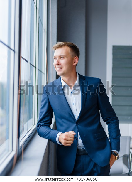 Happy businessman on the office background. Handsome man in a suit. Formalwear concept. Copy space.