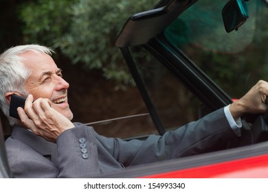 Happy businessman on the phone driving expensive car