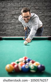 Happy businessman playing a game of billiards and preparing to break pyramid of balls on the pool table.