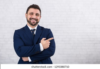 Happy businessman pointing finger away on copy space over brick wall