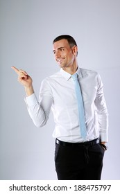 Happy businessman pointing at something on gray background
