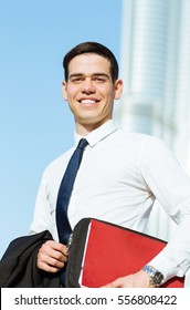 Happy businessman portrait with a modern city background.