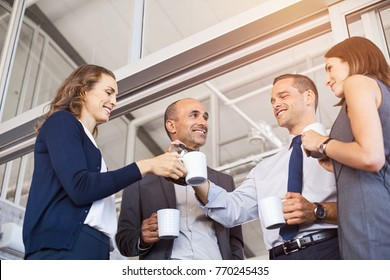Happy businessman pouring coffee to his colleagues in meeting room. Smiling group of businessmen and businesswoman relaxing. Low angle view of formal business team take a coffe break after work.