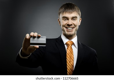 happy businessman reach out on camera and show credit card or visiting card, smile