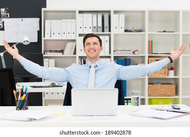 Happy businessman rejoicing in the office sitting at his desk with his arms outstretched smiling and looking up into the air