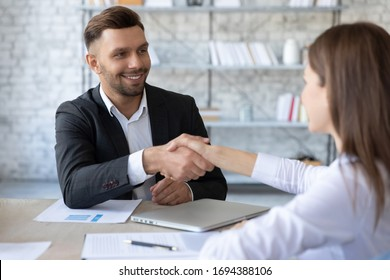 Happy businessman shaking hands with woman job seeker in suit. Smiling successful manager making deal with female partner near laptop. Professional employee holding cv and congratulations applicant.
