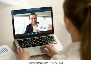 Happy businessman showing positive financial report to remote colleague via video conference call. Project manager proudly shows successful results over webcam application. Closeup view over shoulder.