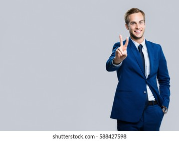 Happy businessman showing two fingers or victory gesture, against grey background. Success in business, job and education concept. Blank copyspace area for advertisiment, slogan or text.
