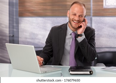 Happy businessman sitting at desk in office, talking on mobilephone, smiling happy.