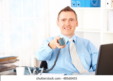 Happy businessman sitting at desk in office giving landline phone. Documents in background, laptop and other equipment on the table.