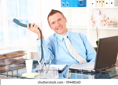 Happy businessman sitting at desk in office, talking on landline phone with laptop and smiling. Documents in background.