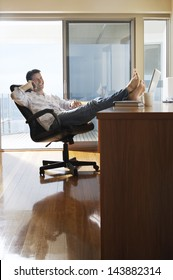 Happy businessman sitting with feet up on desk using mobile phone