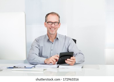 Happy Businessman Sitting In Front Of Computer Holding Calculator