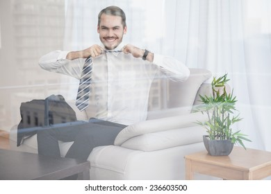 Happy businessman sitting on his couch seen through glass at home in the living room