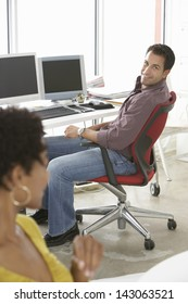 Happy businessman sitting on office chair with female colleague in foreground