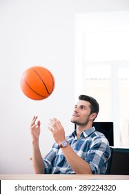 Happy businessman sitting at the table and throwing ball in office
