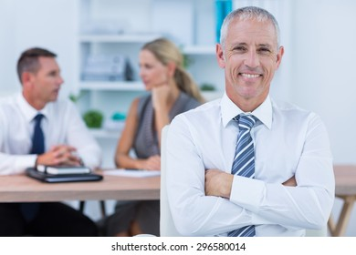 Happy businessman smiling at camera with colleagues behind in the office