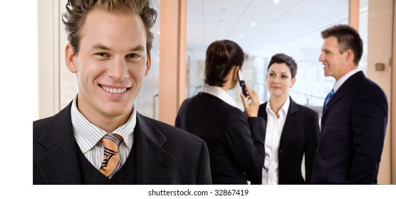 Happy businessman smiling in front, other businesspeople talking in the background.