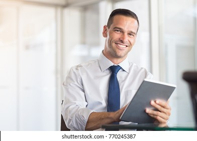 Happy businessman smiling and using digital tablet in his new office. Confident mid business man working on computer and looking at camera. Portrait of successful and proud man in modern office.
