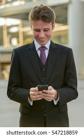 Happy businessman smiling and using mobile phone in front of modern building at Bangkok city