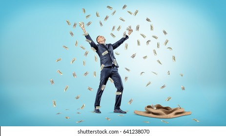 A happy businessman standing beside an empty sack with hands raised up while catching falling dollar bills. Winning lottery. Money shower. Success and fortune.
