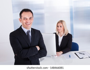 Happy Businessman Standing In Front Of His Colleague Using Computer