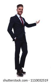 happy businessman standing with hands in pockets on white background while wearing a navy colored suit and a red tie. He is presenting with his hand