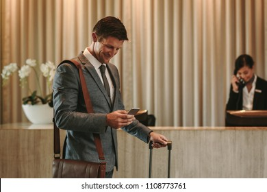 Happy businessman standing in hotel lobby and using mobile phone. Business traveler arriving at his hotel with phone and suitcase.