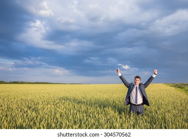Happy businessman standing on the field to face the sky