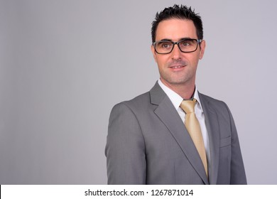 Happy businessman in suit smiling and thinking with eyeglasses