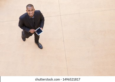 Happy businessman with tablet walking through office hall. Top view of young African American business man holding digital device, looking at camera and smiling. Top view of businessman concept