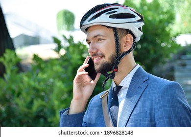 Happy businessman talking on cellphone in park. Business and urban style concept. Close up