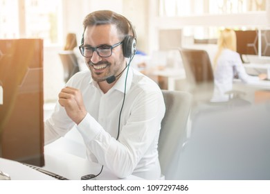 Happy businessman talking on headset in office. Through glass view