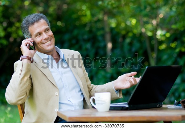 Happy businessman talking on mobile while working outdoor