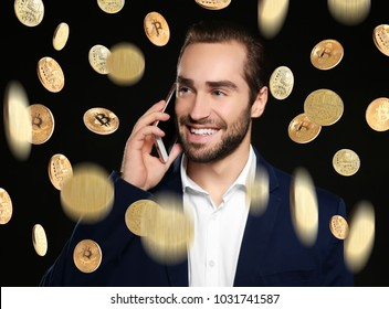 Happy businessman talking on phone and bitcoins falling against black background