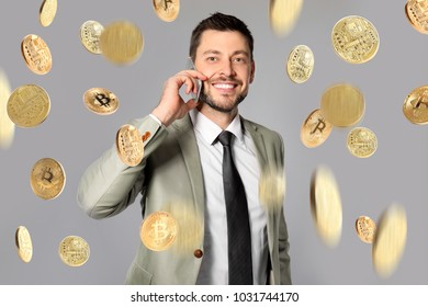 Happy businessman talking on phone and bitcoins falling against grey background