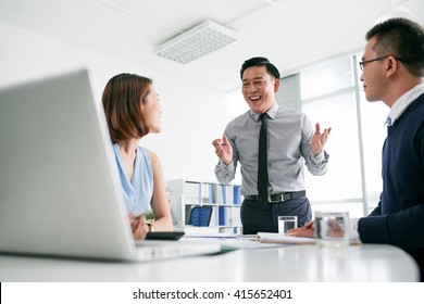 Happy businessman telling good news to his colleagues