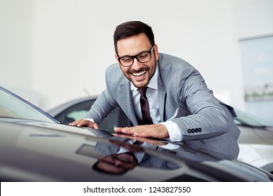 Happy businessman touching car in auto show or salon