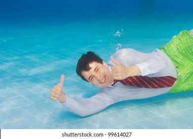 Happy businessman underwater with thumbs up swimming underwater in the pool