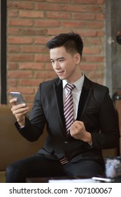 Happy  businessman using cellphone while sitting on sofa at his modern home.Concept of young people working on mobile devices.Blurred background