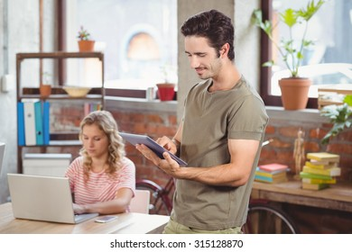 Happy businessman using digital tablet while colleague seen in background in bright office