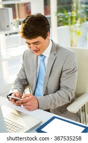 Happy businessman using his phone in office