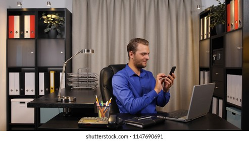 Happy Businessman Using Mobile Phone Working Online While Sitting in Corporate Office Room