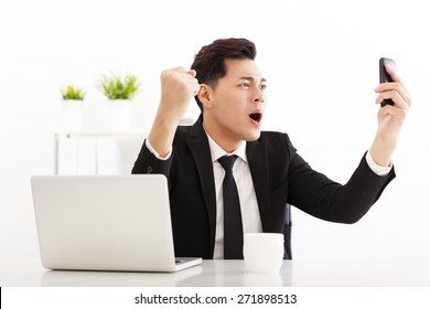 happy businessman watching the smart phone in  office